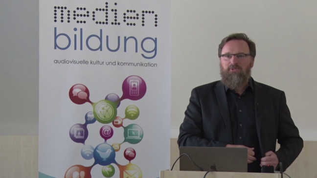 Vortrag Studiengangskonferenz - Benjamin Jörissen steht neben dem Medienbildungbanner am Pult